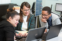 three students share a laptop computer